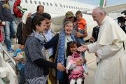 Pope Francis welcomes a group of Syrian migrants at Rome's Ciampino airport on April 16, 2016 following a visit to the Greek island of Lesbos.