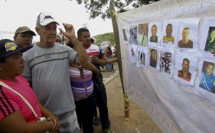 People look at displayed pictures of missing miners in Tumeremo in Bolivar, Venezuela.