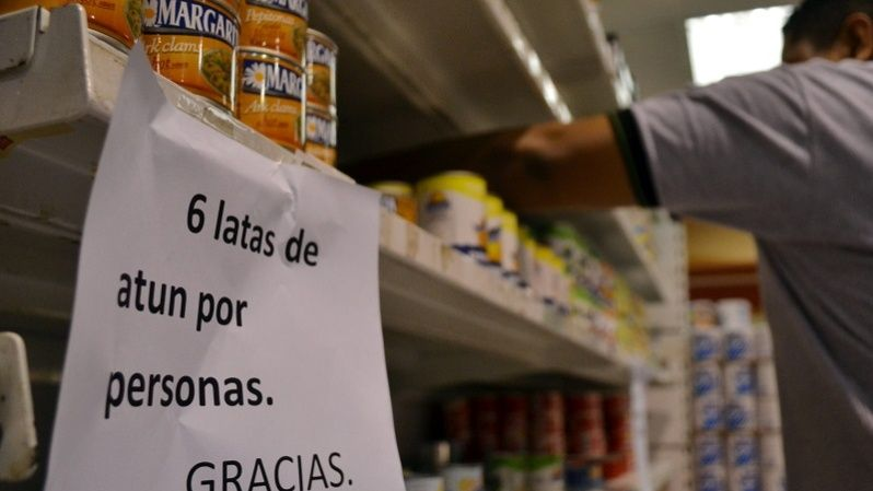 Sign advises shoppers they cannot buy more than six cans of tuna.