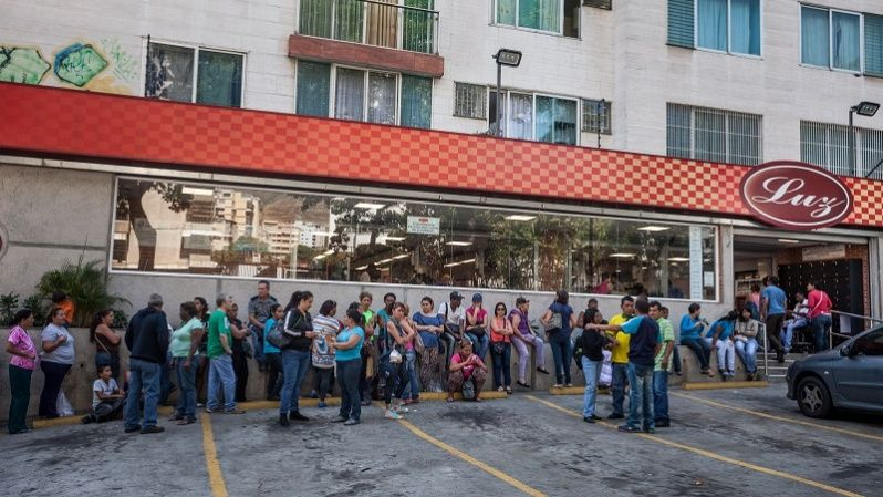 Dozens of people line up in Caracas to buy groceries.