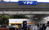 People walk past a YPF petrol station in Buenos Aires Nov. 26, 2013.