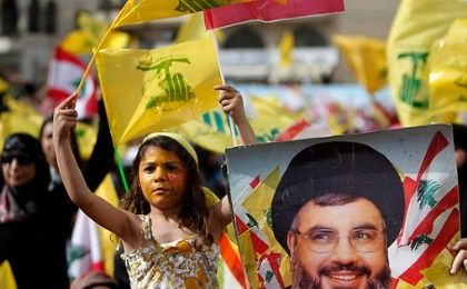 Hezbollah supporters hold posters of group