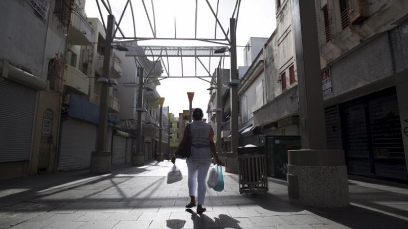 A woman carries bags while walking in a commercial area with stores either closed or offered for sale in San Juan, Puerto Rico, July 31, 2015.