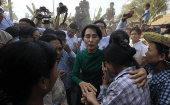 Myanmar pro-democracy Leader Aung San Suu Kyi comforts a woman at a village in Sarlingyi township.
