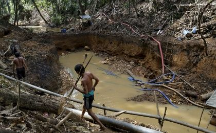 Yanomami indians follow agents of Brazil's environmental agency in an illegal gold mine in the heart of the Amazon rainforest, in Roraima state, Brazil.