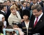 Former Turkish Prime Minister Ahmet Davutoglu and German Chancellor Angela Merkel pose for a picture with refugees in Nizip refugee camp