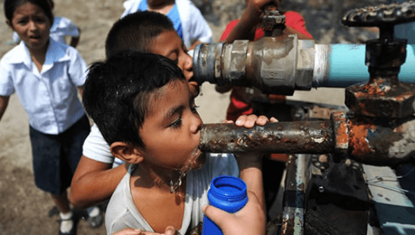 Salvadoran children drink water from a pipe, March 20, 2013.