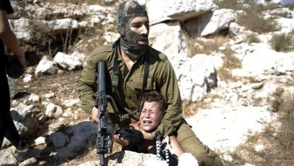 An Israeli soldier detains a Palestinian boy during a protest against Jewish settlements in the West Bank.