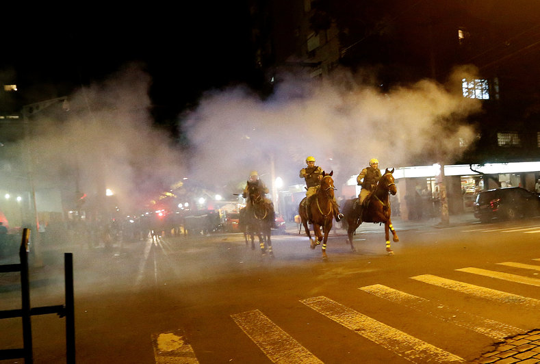Policemen ride their horses during a clash with demonstrators at a protest against the impeachment of President Dilma Rousseff, in Porto Alegre, Brazil, May 12, 2016.