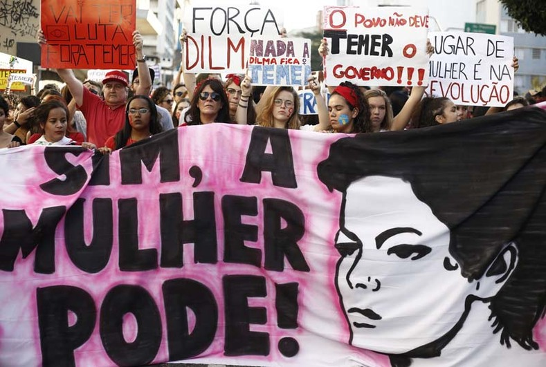 "Demonstrators hold a banner reading ""Yes women can!"" in a protest against Brazil"