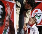 A Palestinian takes part with his daughter in a tribute for late Venezuelan President Hugo Chavez in Gaza City on 7 March 2013.