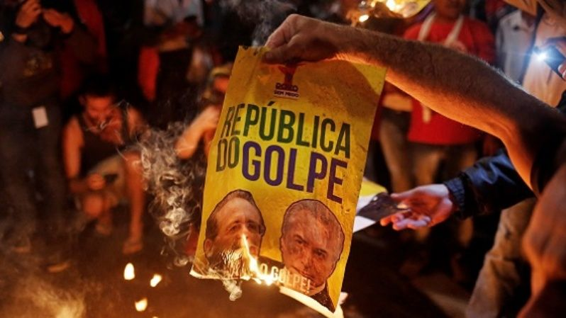 Demonstrators burn a poster with the images of President of the Brazilian Senate Renan Calheiros (L) and Brazil