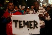 Members of Brazil's Homeless Workers' Movement hold a banner with the name of interim President Michel Temer during a protest in Sao Paulo, May 12, 2016.