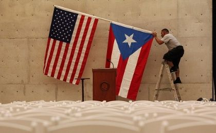 A worker takes off the U.S and Puerto Rican flag after a rally of U.S. Democratic presidential candidate Bernie Sanders in San Juan.