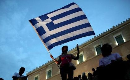 An anti-austerity protester holds a Greek flag in front of the parliament during a protest against austerity policies on last summer.