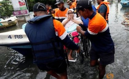 Sri Lankan navy personnel carry a woman on a wheelchair on a flooded road in Wellampitiya, Sri Lanka May 21, 2016.