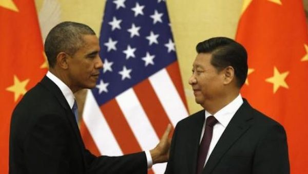 U.S. President Barack Obama pats Chinese President Xi Jinping on the shoulder at the end of their news conference in the Great Hall of the People in Beijing Nov. 12, 2014.