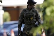 A federal police officer walks in front of the home of former house speaker Eduardo Cunha during a raid in Brasilia, Brazil, Dec. 15, 2015.