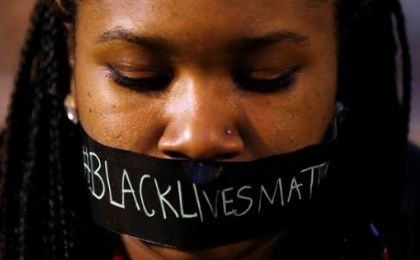 A protester wears tape over her mouth during a silent demonstration against what they say is police brutality after the Ferguson shooting of Michael Brown March 14, 2015.