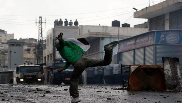 A Palestinian protester throws a stone towards Israeli police vehicles during clashes in Shuafat refugee camp in the West Bank near Jerusalem.