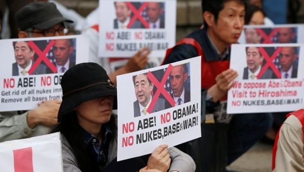 Protesters hold placards at the Peace Memorial Park in Hiroshima.