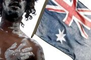 An Indigenuos Australian performer stands in front of an Australian flag