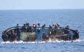Migrants fall into the sea from a boat that capsized last week as Italian navy ships attempted a rescue.