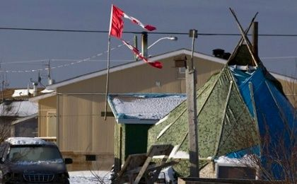 A tattered Canadian flag flies over a teepee in Attawapiskat, Ontario.