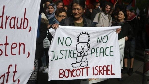 An activist holds a sign calling for the boycott of Israel.