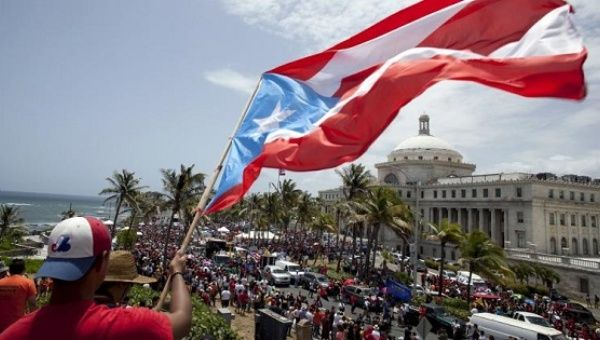 A man waves a Puerto Rico flag in San Juan as demonstrators protest austerity measures imposed because of the U.S. territory