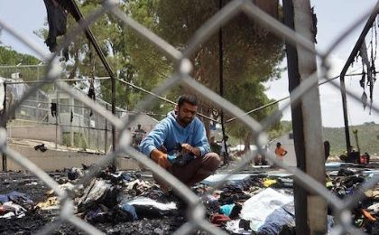 A migrant searches through the debris of a torched tent in the Moria detention camp on the Greek island of Lesbos on Thursday f