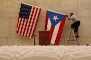 A worker takes off U.S and Puerto Rican flag after rally of U.S. Democratic presidential candidate Bernie Sanders in San Juan, Puerto Rico.