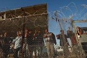 Palestinians stand behind a fence in the southern Gaza Strip May 12, 2016.