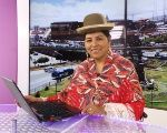Bertha wears the traditional cholita dress and bowler hat while presenting the news.