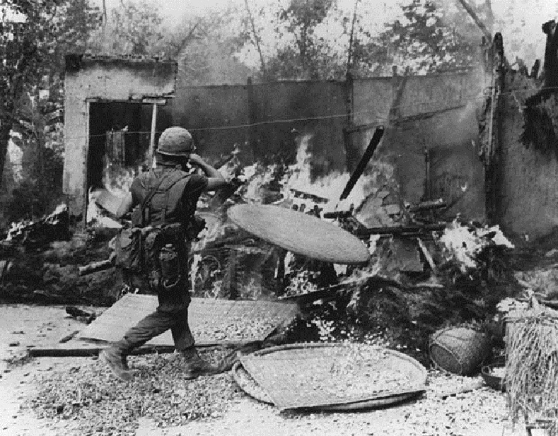 A soldier burning down a hut in My Lai village, Vietnam.
