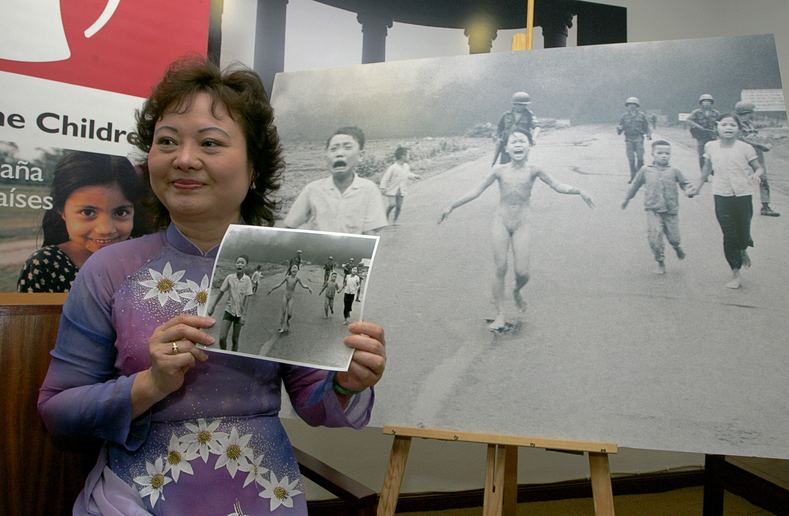 "Phan Thị Kim Phúc, also known as ""Napalm Girl,"" poses with the iconic photo taken in Trang Bang by AP photographer Nick Ut which showed her at nine years of age running naked on a road after being severely burned by a South Vietnamese napalm attack."