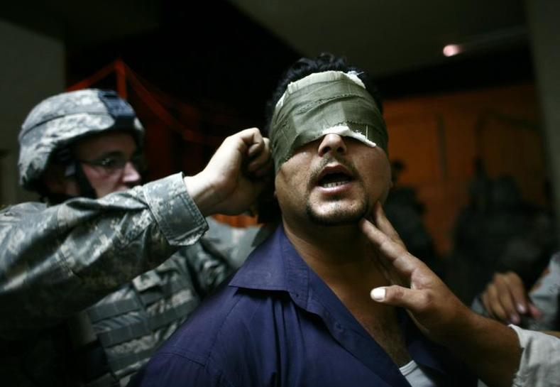 U.S. soldiers blindfold an Iraqi man after arresting him during a night patrol at the Zafraniya neighborhood, southeast of Baghdad September 4, 2007.