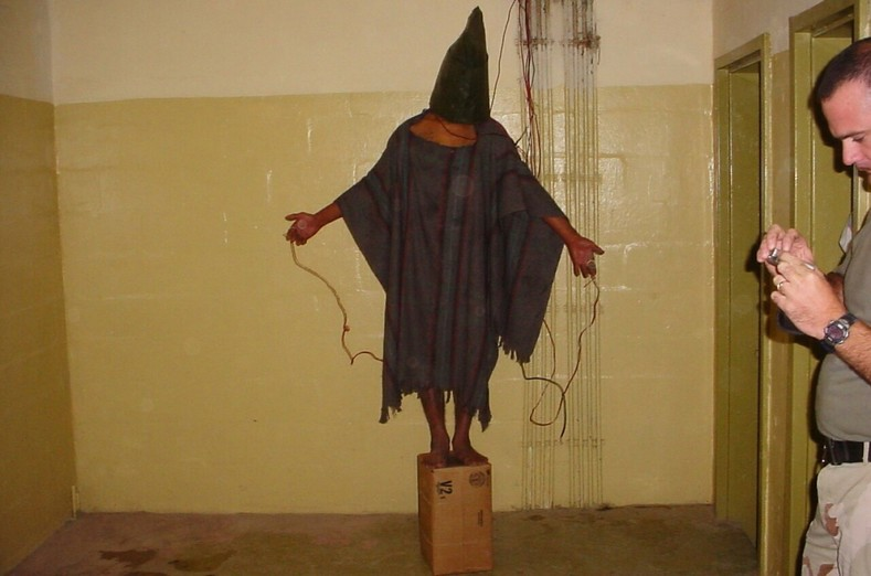 An unidentified detainee standing on a box with a bag on his head and wires attached.