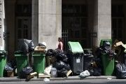 Pedestrians walk past trash piling up on the pavement of rue Des Petits Champs in central Paris on June 8, 2016.