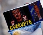 A demonstrator holds up a placard with images depicting Argentine President Mauricio Macri with the word