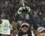 The Seattle Seahawk's Richard Sherman holding up the National Football Conference championship trophy, 2013.