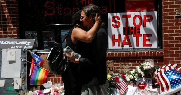 Matti Mejia (L) and Shaina Roberts embrace after laying flowers at The Stonewall Inn in memory of the victims of the Orlando massacre, June 13, 2016.