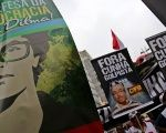 Protesters carry signs in favor of Dilma Rousseff and against Eduardo Cunha during a protest against the impeachment process in Sao Paulo, Dec. 16, 2015.