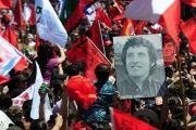 People hold the portrait of Chilean singer Victor Jara, during a funeral ceremony in Santiago, Dec. 5, 2009.