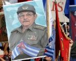 People carry pictures of Cuba's president Raul Castro and his brother and Cuba's former President Fidel Castro during a parade in Havana