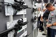Gun enthusiasts look over Sig Sauers guns at the National Rifle Association's annual meetings and exhibits show in Louisville, Kentucky, May 21, 2016.