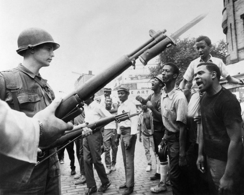 "The attitude and phrase ""Black power"" signaled a massive radicalization of Black people within the United States, whose patience was stretched to the breaking point by racist repression, systemic neglect and abuse. Black demonstrators face armed federal soldiers in Newark, N.J., on July 17, 1967, during riots that erupted following a police operation. Unrest in cities across the U.S. in 1967 led President Johnson to strike the National Advisory Commission on Civil Disorders, also known as the Kerner Commission."