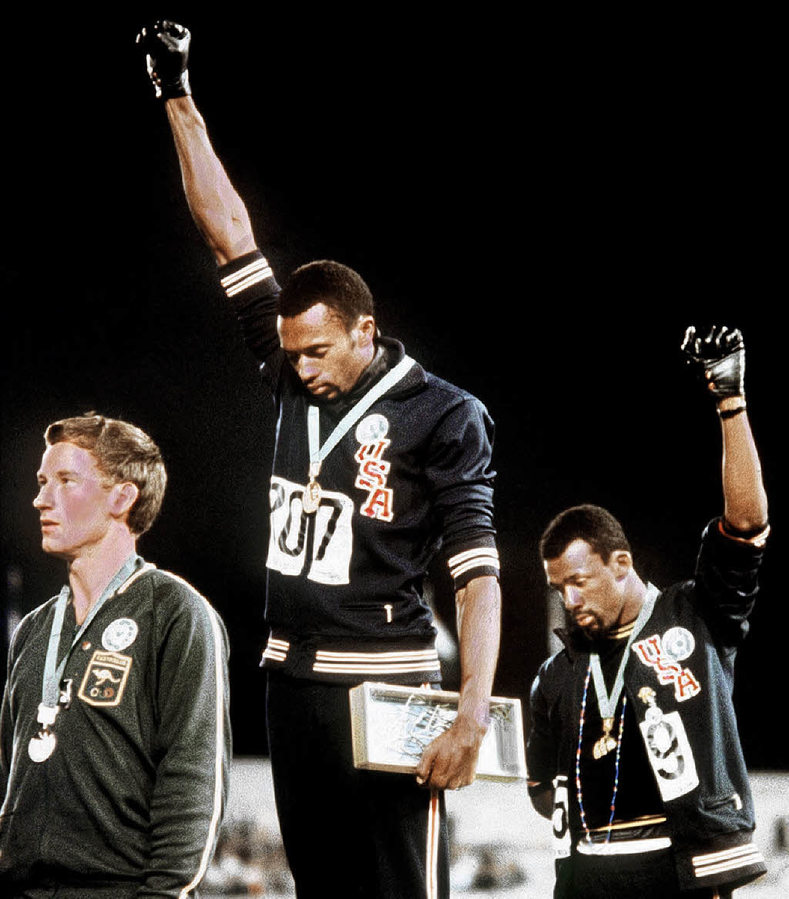 Gold medallist Tommie Smith (center) and bronze medalist John Carlos (right) showing the raised fist on the podium after the 200 m race at the 1968 Summer Olympics in Mexico; both wear Olympic Project for Human Rights badges. Peter Norman (silver medalist, left) from Australia also wears an OPHR badge in solidarity to Smith and Carlos.