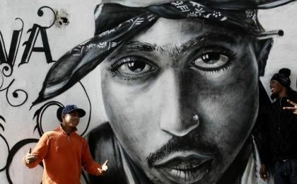 "Nuno (L) talks to Sergio Rodrigues ""Sorriso"" next to a graffiti of murdered rapper Tupac Shakur in the Cova da Moura district in Lisbon December 6, 2007."