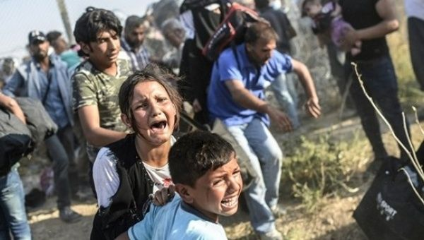 Syrian children fleeing the war cry after passing through broken down border fences to enter Turkey.